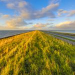 Afsluitdijk dutch dike with motorway and cycling track at sunset with clouded sky