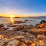 Peloponnese coast near Skala with red rocks on shore at sunrise
