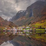 Small homes on the shore of a fjord photographed from a Fjords sightseeing cruise boat leaving Flam in autumn, Norway