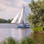Traditional 'flat bottom' sailing yacht cruising on the lakes in Friesland, The Netherlands.