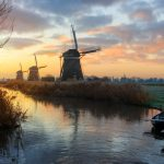 Three windmills, two rowboats and a canal in a rural landscape in Leidschendam, the Netherlands at sunrise in winter.